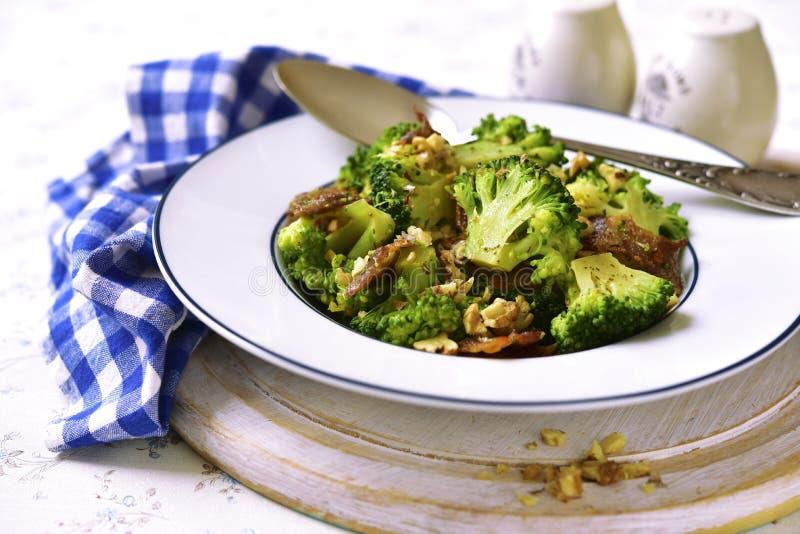 Brokkoli mit gebratenem Speck und Walnüssen stockbild