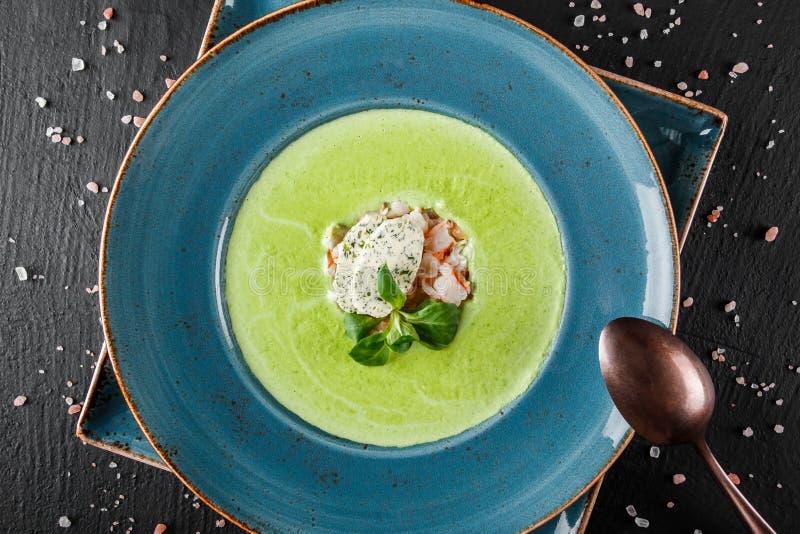 Brokkoligr?ne Sahnesuppe mit Garnele und K?se in der Platte auf dunklem Steinhintergrund Sauberes Essen, gesundes Lebensmittelkon stockbilder