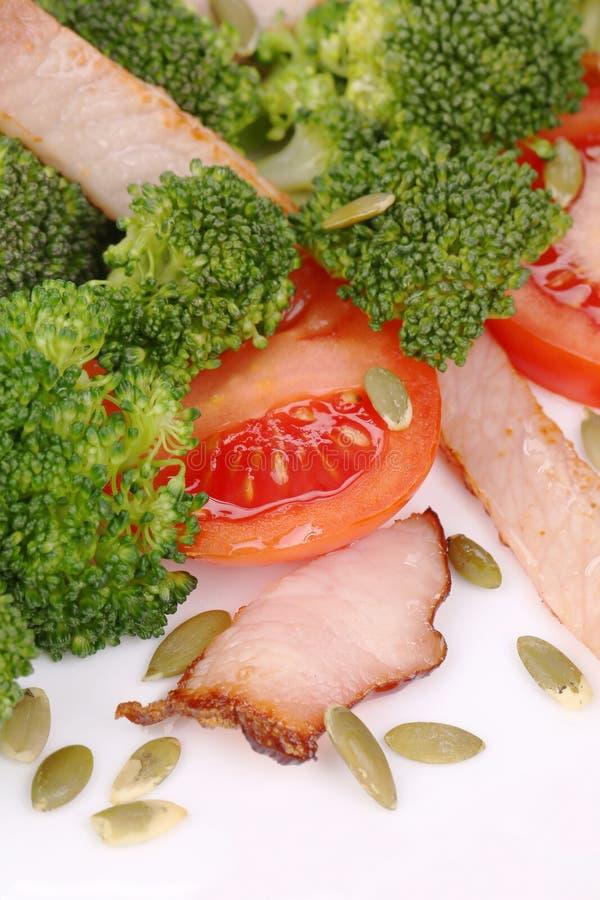 Brokkolisalat mit Kürbiskernen und Tomaten stockbild