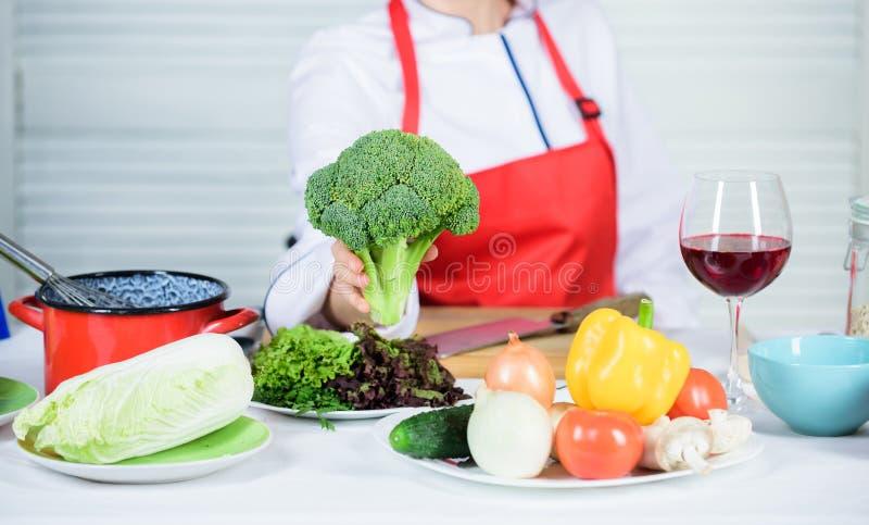 Brokułu odżywiania wartość surowa karmowa dieta Kobieta szefa kuchni fachowego chwyta surowi brokuły jarzynowi Bezpłatny zdrowy j zdjęcia royalty free