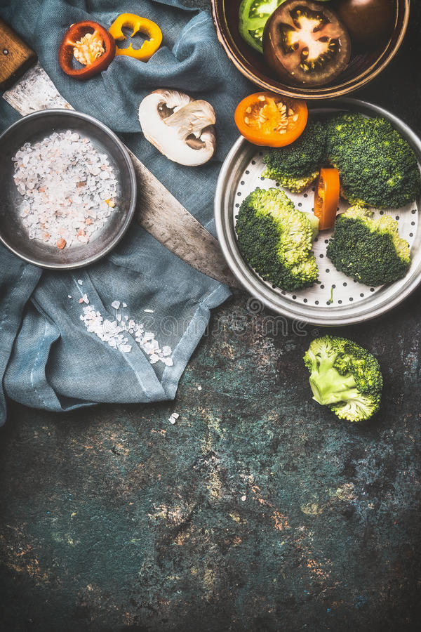 Brokuły, szampinion pieczarka i inni jarscy kulinarni składniki z kuchennym nożem na ciemnym nieociosanym tle, odgórny widok, b zdjęcie royalty free