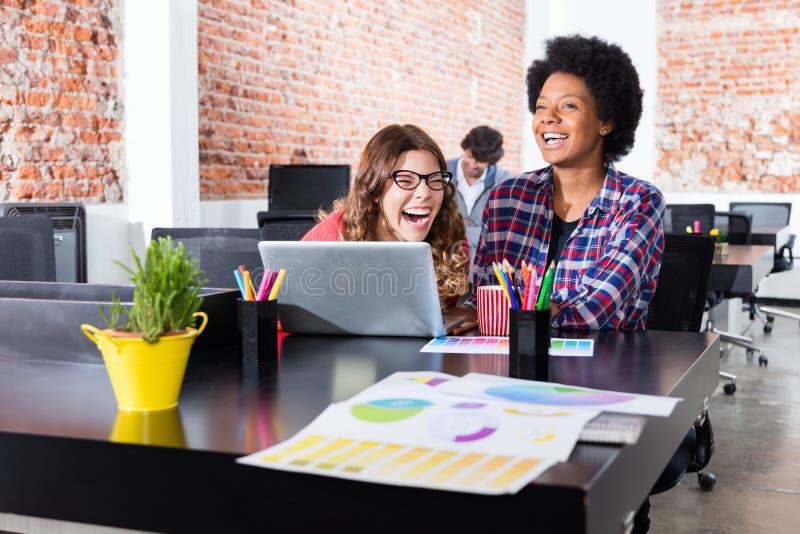 Broma de risa de la diversión de los colegas del ordenador portátil del escritorio de oficina de la gente que se sienta imagen de archivo libre de regalías