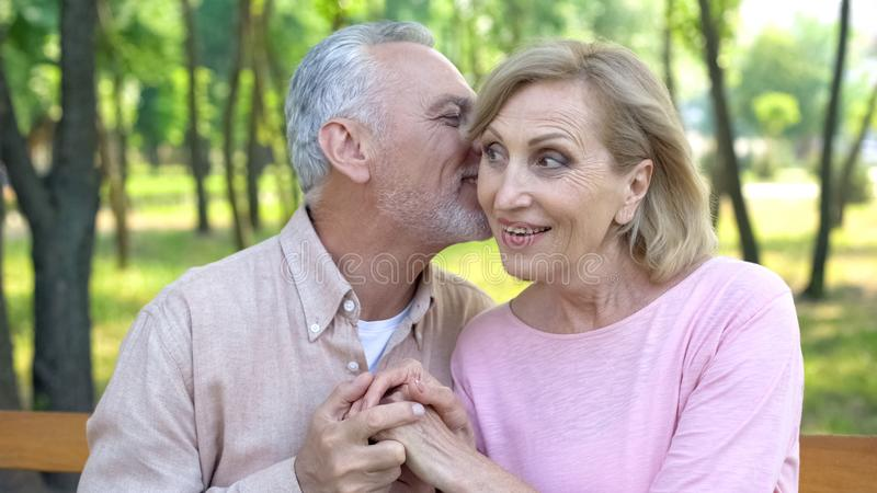 Bromas susurrantes del hombre mayor, ligando con la mujer, amor maduro, felicidad de la edad avanzada fotografía de archivo