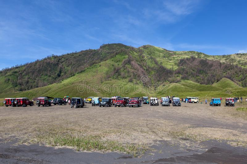 Bromo-Tengger-Semeru NP, JAVA/INDONESIA - April. Bromo-Tengger-Semeru NP, JAVA/INDONESIA - April 17, 2015: Tourist jeeps in savanna of Tengger caldera near stock images