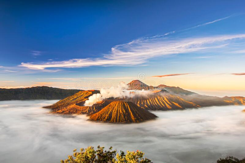 Bromo volcano crater erupt release smoke with sunrise sky background and morning fog landscape at Indonesia Bromo national park. Bromo volcano crater erupt royalty free stock photos