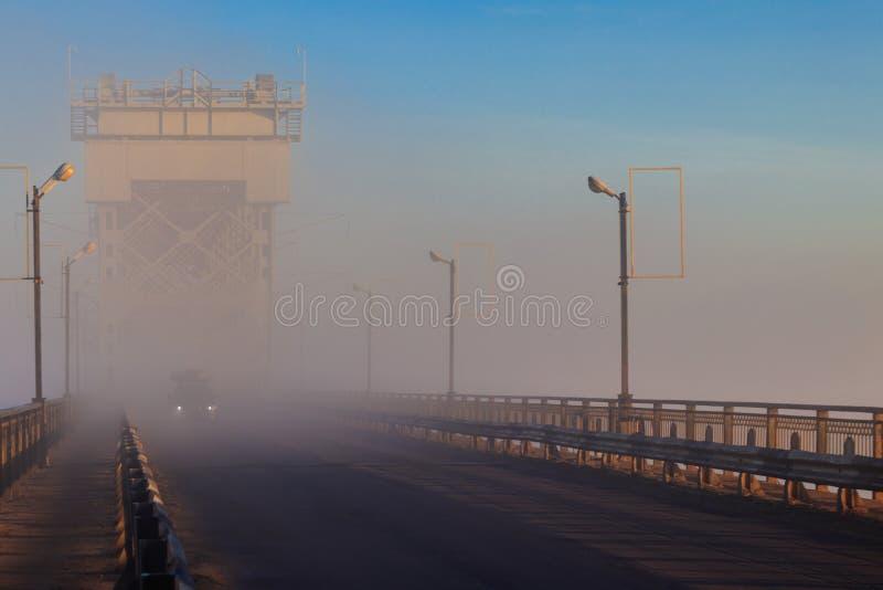 Bron över floden Dnieper i dimma på hösten Kremenchug, Ukraina arkivfoto