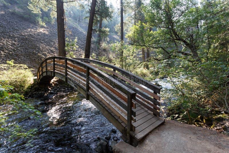 Bron över vatten, som flödar in i McArthur-Burney, faller i alpin skog för Lassen vulkanisk nationalpark` s royaltyfri bild