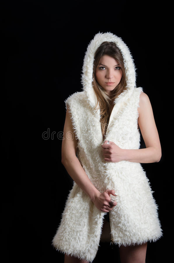 Bronde woman wear only a mouton sleeveless jacket. Pose against a dark black background royalty free stock image