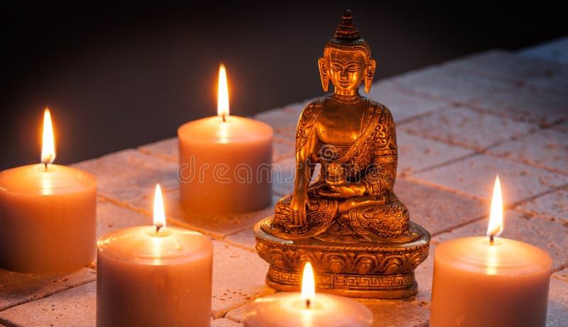 Brons Boedha met warme aangestoken kaarsen over kalksteenachtergrond stock afbeelding