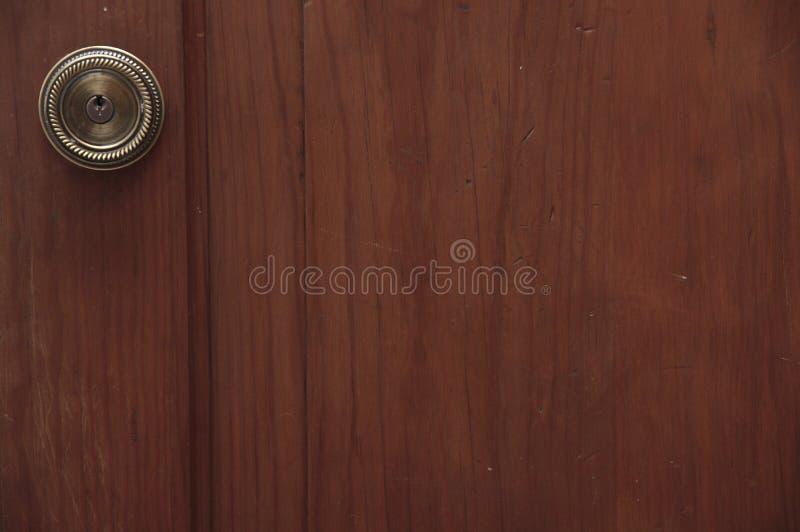 Brons dörrhandtaget på en trädörr arkivfoto