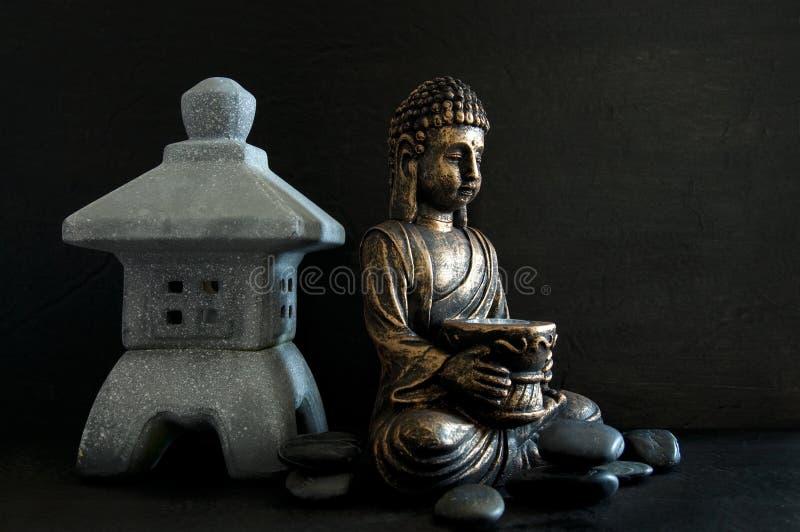 Brons Gautama Buddha en Miniatuurtempel met Donkere die Rotsen op Zwarte worden geïsoleerd stock fotografie