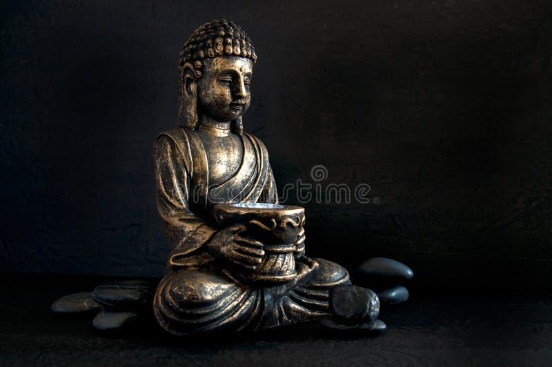 Brons Gautama Buddha met Donkere die Rotsen op Zwarte wordt geïsoleerd stock afbeelding