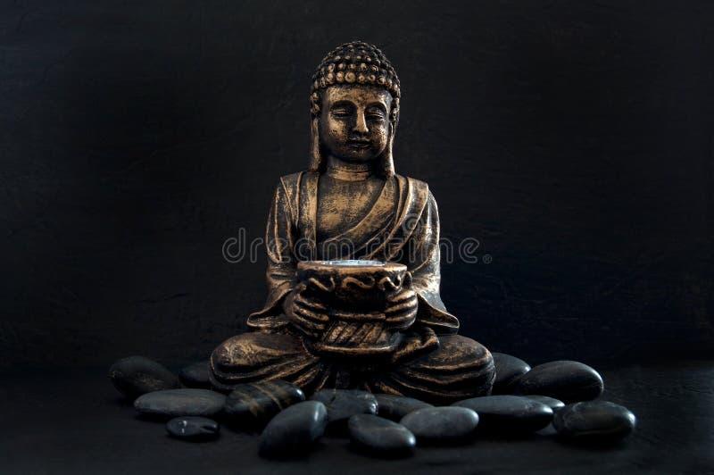 Brons Gautama Buddha met Donkere die Rotsen op Zwarte wordt ge?soleerd stock afbeeldingen