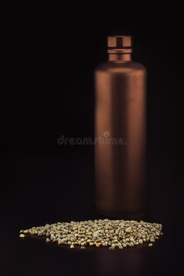 Brons-gekleurde ceramische fles en hennepzaden stock foto