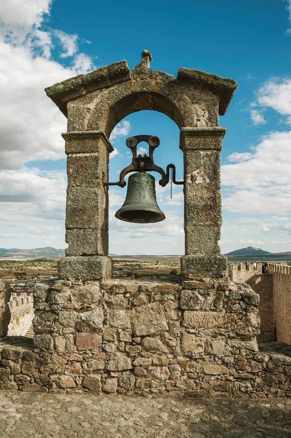 Brons klockan överst av stenväggen på slotten av Trujillo royaltyfri bild