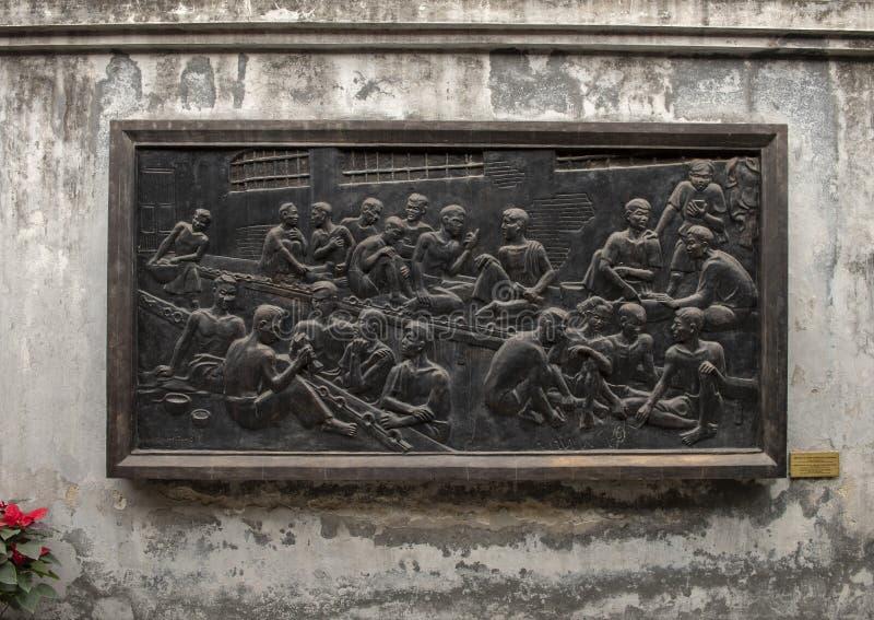 Brons lättnad i det Hoa Lo fängelset som firar minnet av vända fängelset in i en skola för att fortplanta det revolutionära argum royaltyfri foto