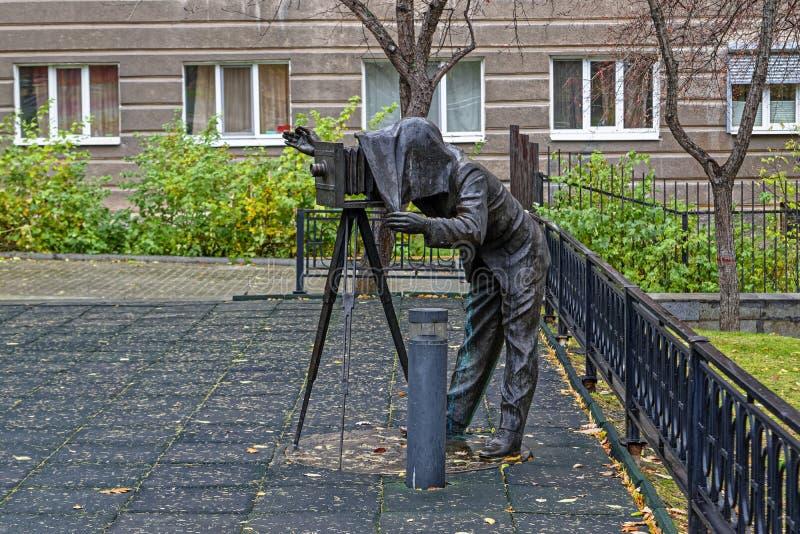 Brons skulptur av en fotograf med en tappningkamera i parkerar royaltyfria foton