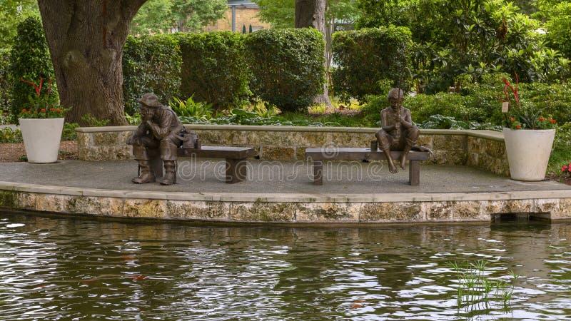 Brons skulptur av ett pojke- och gamal manfiske av Gary Price på Dallas Arboretum och botaniska trädgården royaltyfria bilder