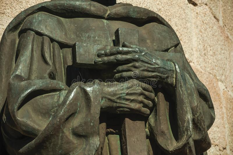 Brons statydetaljen av prästhänder som rymmer ett kors på Caceres arkivfoton