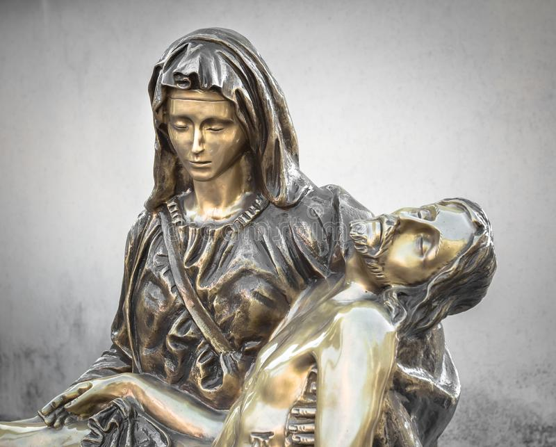 Brons statyn av döda Jesus Christ som omfamnas av oskulden Mary royaltyfria bilder