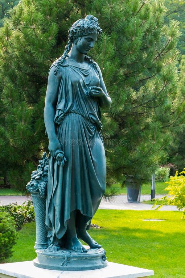 Brons statyn av en kvinna med en korg av blommor i parkera på bakgrunden av ett fluffigt sörjer arkivbild