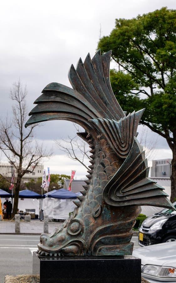Brons statyn av fisken på gatan fotografering för bildbyråer