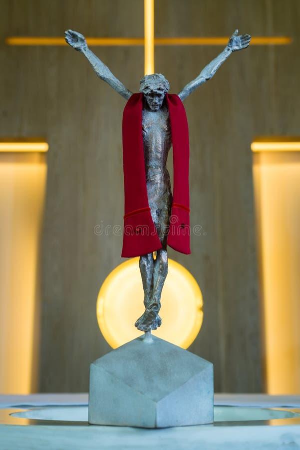 Brons statyn av Jesus Christ korsfäste på ett kors i en kyrka arkivbilder