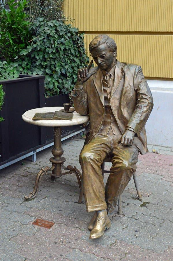Brons statyn av mannen som dricker kaffe på kafétabellen, den Pecs Ungern arkivbilder