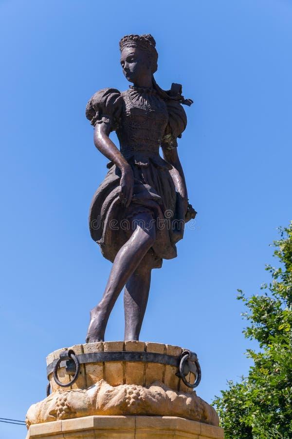Brons statyn av trängande druvor för en flicka i en trähink royaltyfri fotografi