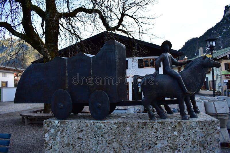 Brons statyn i Oberammergau som visar en vagn arkivfoton