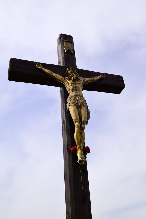 Bronsbeeldhouwwerk van Jesus Hristos op een houten kruis wordt gekruisigd dat stock fotografie