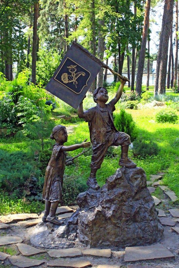 Bronsbeeldhouwwerk van weinig jongen met vlag en meisjes het uitgaan berg in stadspark stock fotografie