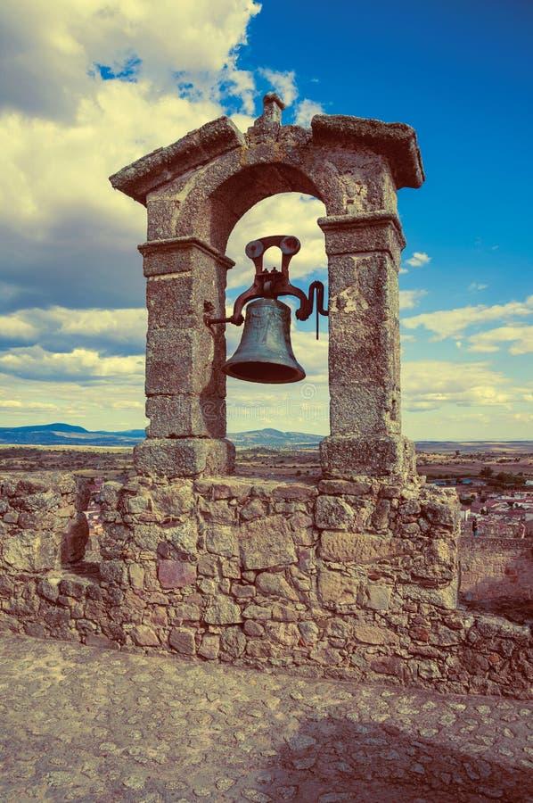 Bronsklok bovenop steenmuur bij het Kasteel van Trujillo royalty-vrije stock afbeelding