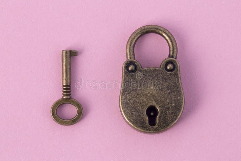 Bronssleutel en hangslot stock afbeelding