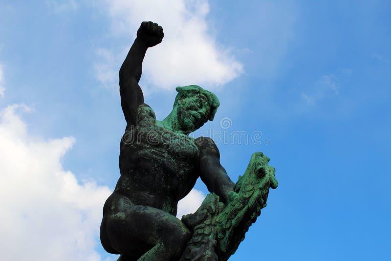 Bronsstandbeeld van een mens die tegen een dier vechten stock foto's