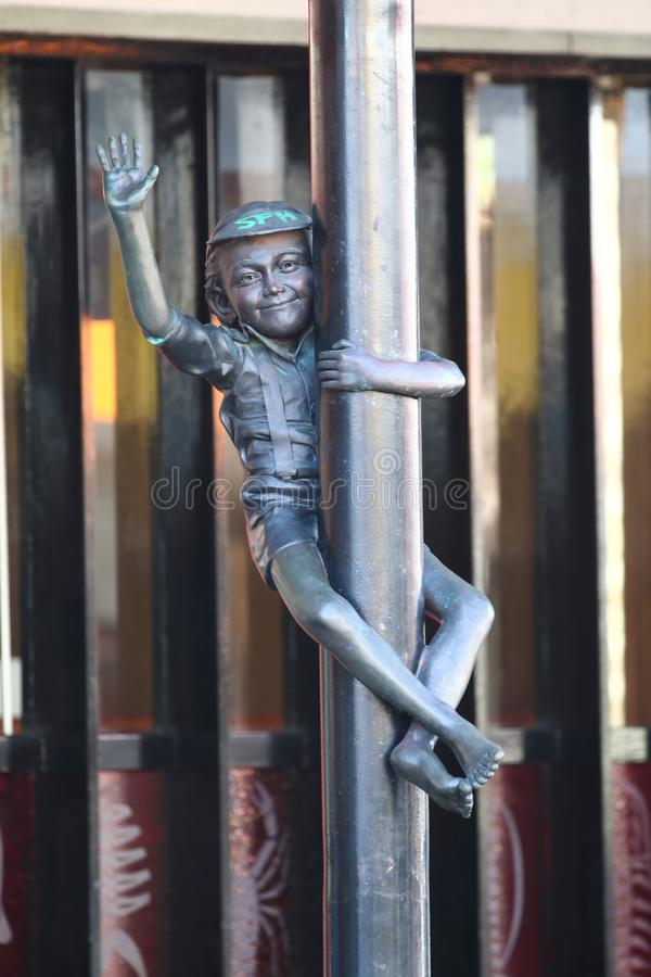 Bronsstandbeeld van weinig jongen die een pool en het golven beklimmen royalty-vrije stock afbeelding
