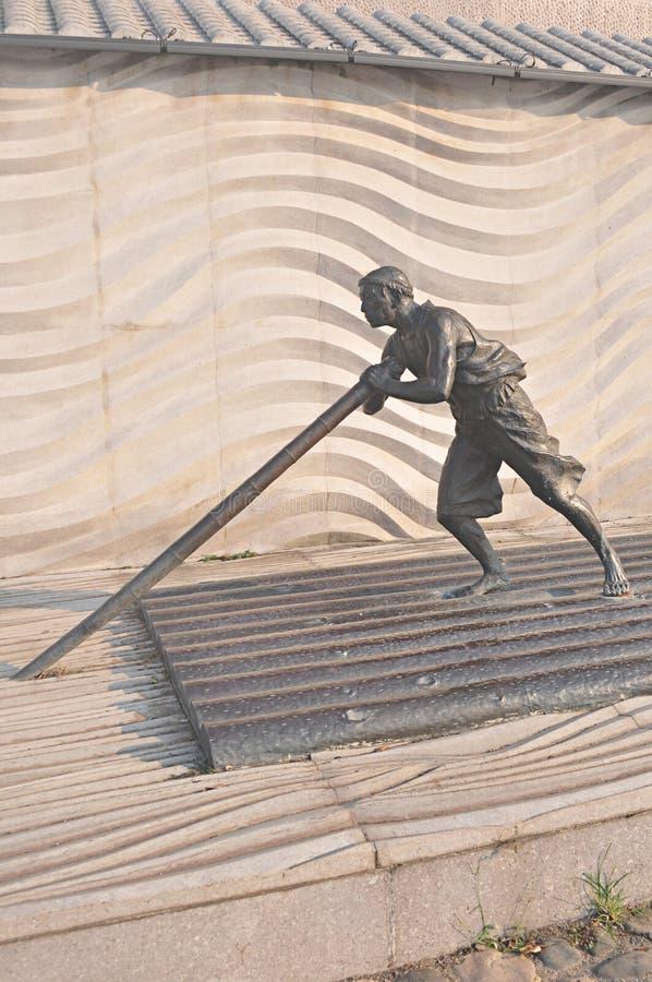 Bronsstandbeelden op houten bootraad met bamboe het rafting, huidig art. royalty-vrije stock afbeelding
