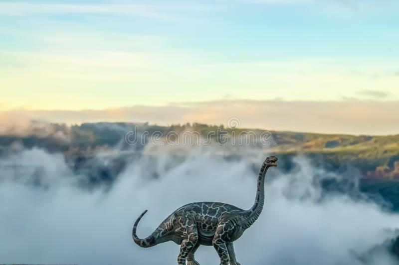A brontosaurus or thunder lizard dinosaur roaring against a blurred misty mountain background - created with a model against natur stock photos