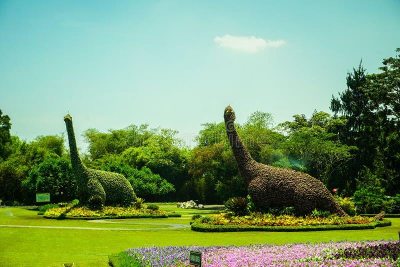 Brontosauruskopiastaty som göras från naturligt grönt skog och träd med klar himmel - foto royaltyfria foton