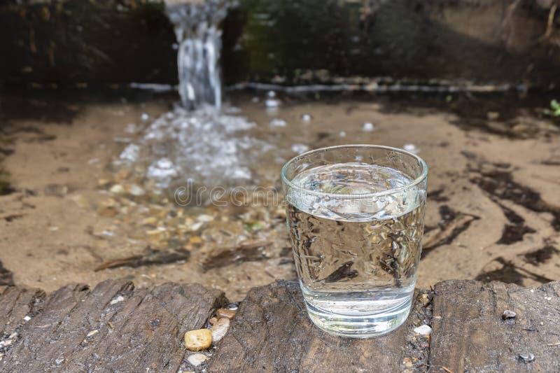 Bronwater Een glas koud water bevindt zich in aard stock foto