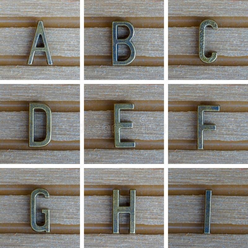 Bronz alfabetbokstav på träbakgrund A B, C, D, E, F, G, royaltyfri foto
