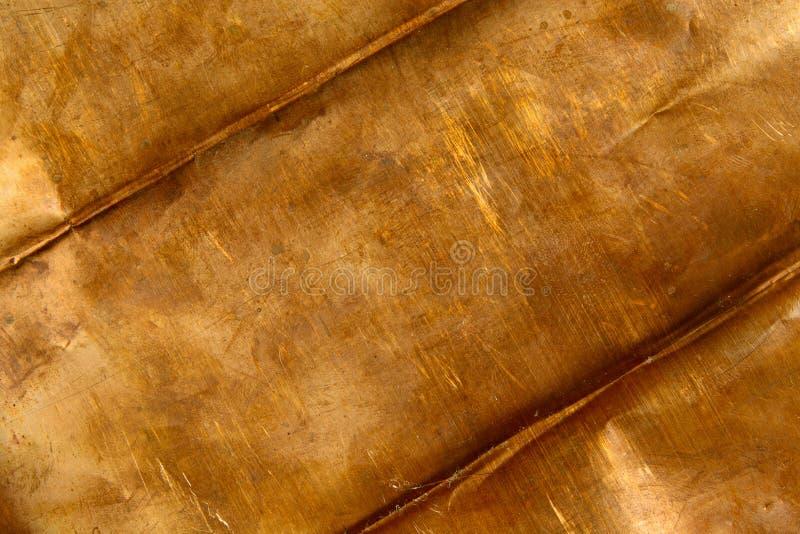Bronze background. Background from crumpled bronze sheet metal stock photos