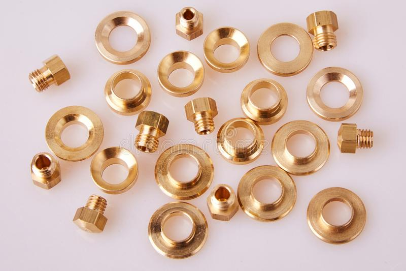 Bronze Brass Flat Washers Hardware Gaskets and GIGLEURs. Close-up, of different sizes scattered a white background. A nozzle jet that is calibrated to stock photos