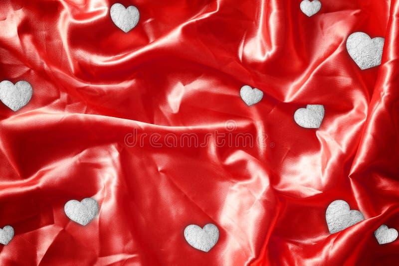 Bronze brilhante da folha do coração na seda vermelha da tela imagem de stock royalty free