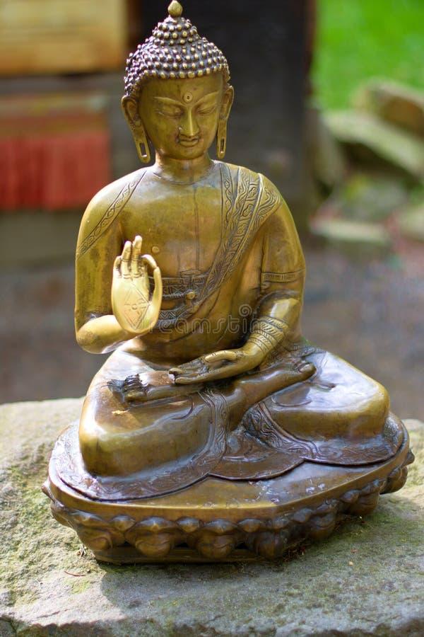Bronze-Buddha, der auf einem Stein sitzt lizenzfreie stockfotos