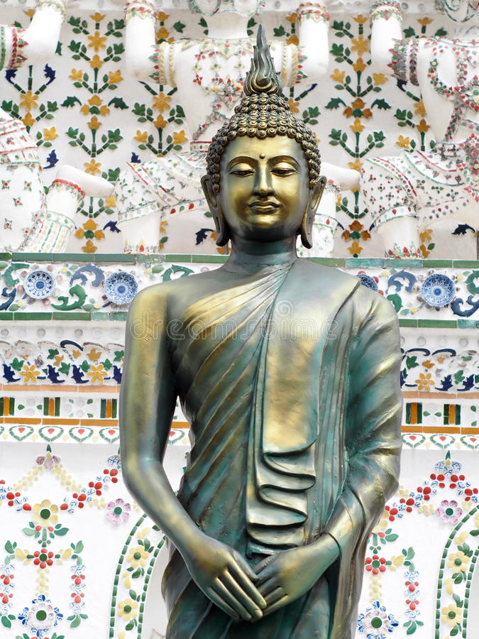 Bronze BUDDHA statue in front of decoration ornament details of famous historic buddhism stupa in WAT ARUN. Close-up on bronze BUDDHA statue in front of royalty free stock photo