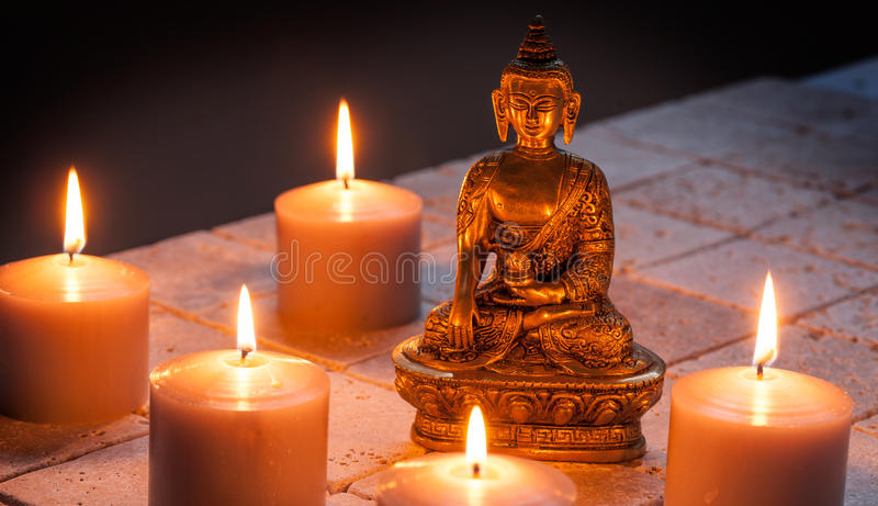 Bronze Buddha with warm lighted candles over limestone background. Bronze Buddha with warm lighted candles for concept of mindfulness and meditation over stock image