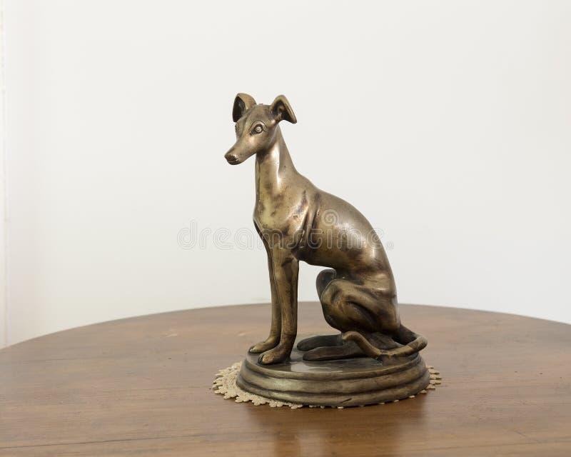 Bronze de um galgo italiano que senta-se em um suporte imagem de stock