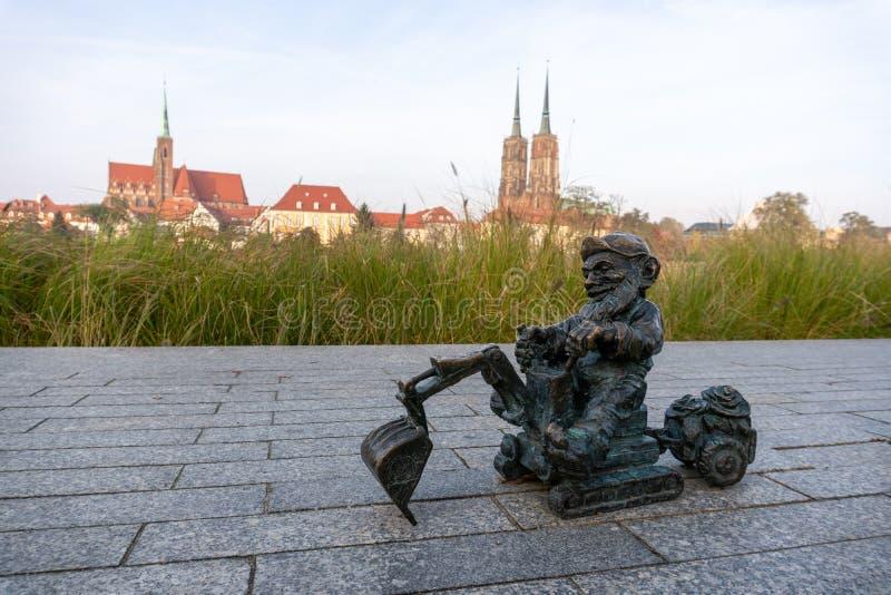 Bronze dwerg aan de start van de rivier Odra met ostrow tumski op de achtergrond Er zijn meer dan 600 dwergen in Wroclaw royalty-vrije stock fotografie