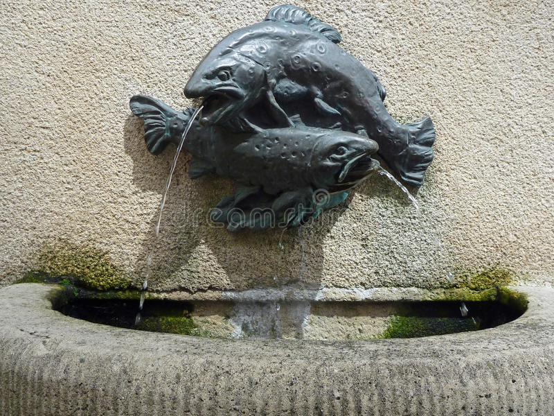 Bronze Fish Fountain. Small bronze fish water spouts on a Greek island village fountain, Lefkada, Greece royalty free stock image